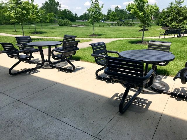 Black dining sets in outdoor patio area with greenery