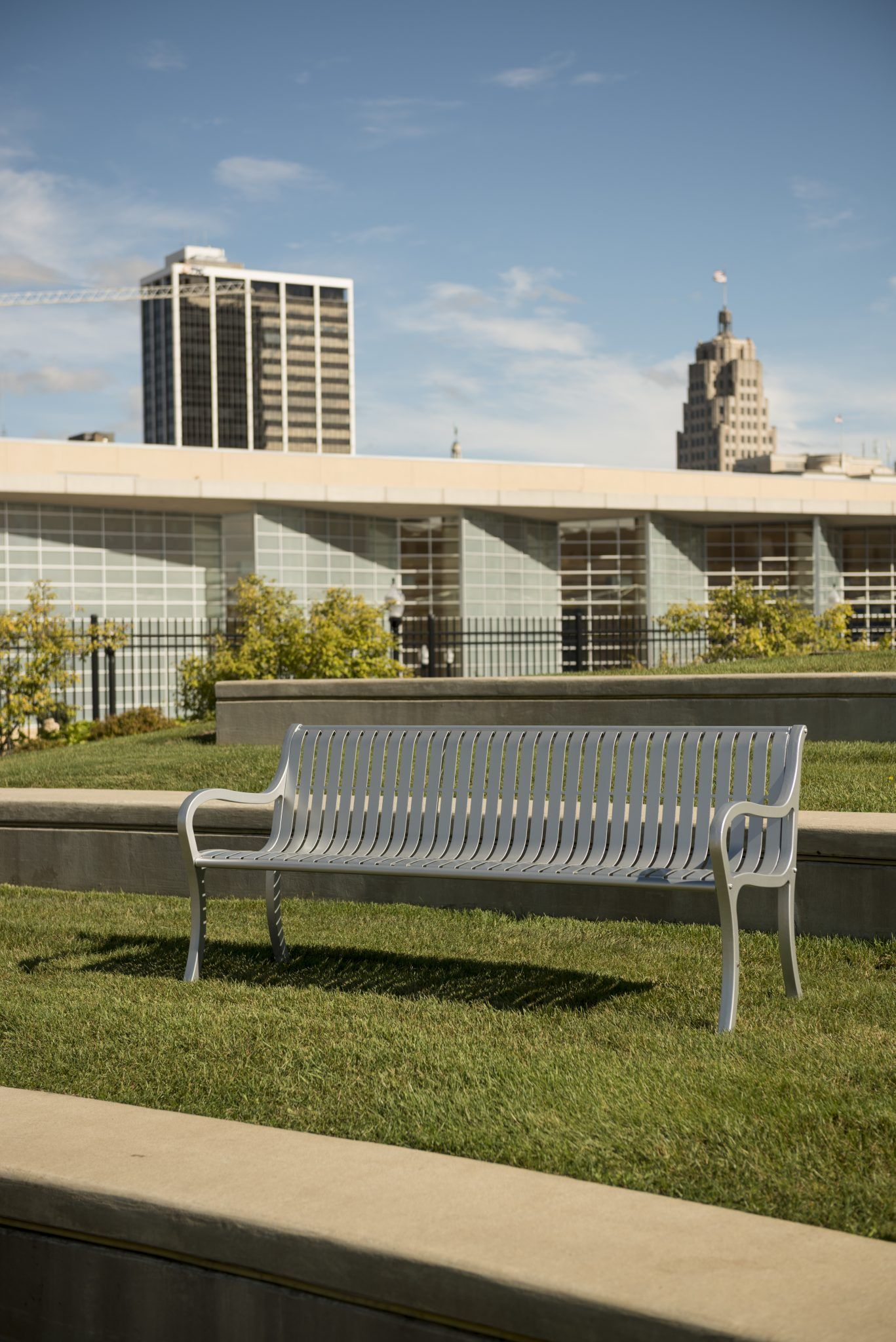 Silver park bench with city sky line